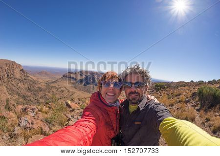Adult couple taking selfie on panoramic viewpoint in Marakele National Park travel destination in South Africa. Concept of adventure and traveling people. Fisheye view in backlight.