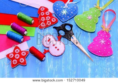 Felt Christmas ornaments. Christmas tree, heart, star, snowman crafts, scissors, sewing kit, felt sheets on blue wooden background. Simple kids crafts