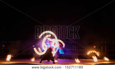 Artists juggling with burning poi's at fire performance. Long exposure causing painting with light.