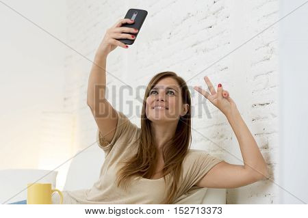 young attractive 30 years old woman playing on home sofa couch taking selfie portrait with mobile phone having fun laughing and smiling happy and playful