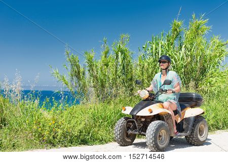 Woman driving quadbike by the sea, toned image