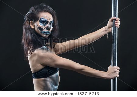 Attractive pole dancer in black sport underwear holds her hands on the pylon in the studio on the dark background. She has a body-art on her body. Girl looks into the camera. Horizontal.