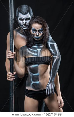 Cute pole dancers with horrific body-art stands next to a pylon on a dark background in the studio. They dressed in black sportswear and hold the right hands on the pylon. Guy hugs the girl. Vertical.