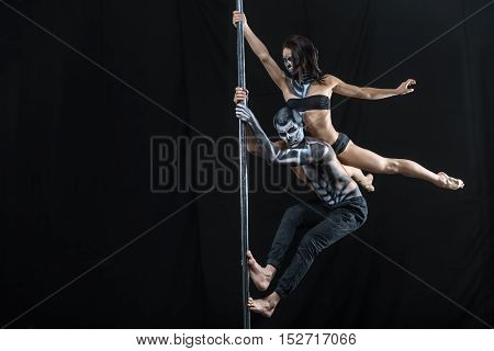 Awesome couple of pole dancers with a horrific body-art in the dark studio. Guy hangs on a pylon and a girl lies on his back and holds the pylon with her right hand. She lies with outstretched legs.