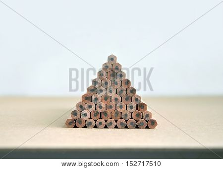 Wooden pencils with gray slate stacked in a pyramid shape on a brown surface in perspective.
