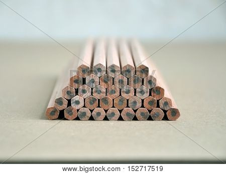 Wooden pencils with gray slate lie on each other on brown surface in perspective.
