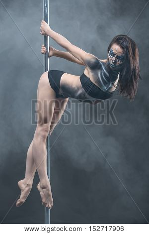 Attractive pole dancer with body-art hangs on a pylon in the studio on the dark background with a cloud of a smoke. She holds the pylon with the hands from the back and looks to the side. Verical.