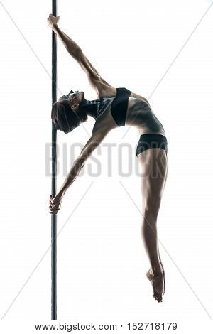 Young pole dancer with a body-art hangs on a pylon in a studio on a white background. She holds her stretched hands on the pylon and her legs are together. Girl wears black sport underwear. Vertical.