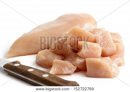 Whole Skinned Deboned Raw Chicken Breast Isolated On White Next To Diced Chicken Breast And Knife.
