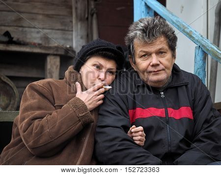 Man and woman nearby. Woman smoking a cigarette. Old wooden house
