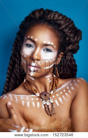 African style woman . Attractive young woman in ethnic jewelry with drum. close up portrait. Portrait of a woman with a painted face. Creative makeup and bright style.