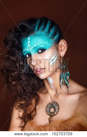 attractive young woman in ethnic jewelry with drum. close up portrait. Beautiful girl shaman. Portrait of a woman with a painted face. Creative makeup and bright style.