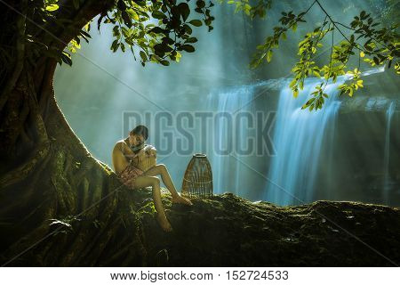 Children in rural sit under a tree on the rocks in a waterfall.