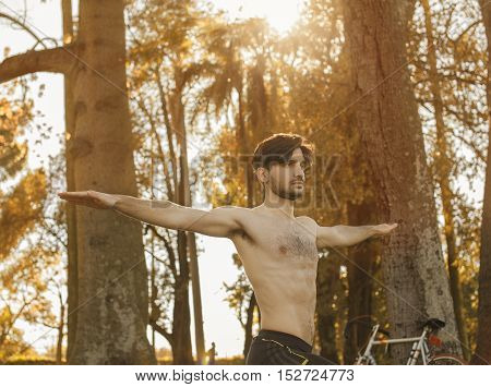 Young handsome hispanic man exercising in the autumn forest with his bycicle on the background. Health concept.