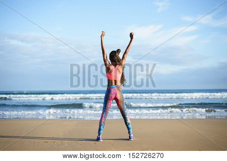 Fitness success and healthy lifestyle motivation. Back view of sporty black woman raising arms to the sky towards the sea for celebrating workout goals.