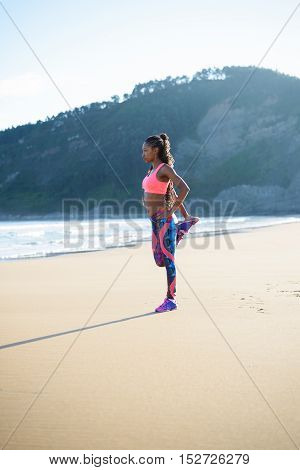 Fitness woman stretching leg at the beach. Black female athlete exercising outdoor against the sea.