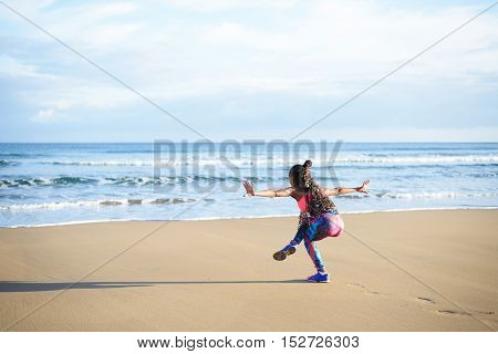 Back view of woman practicing balance yoga exercise towards the sea during fitness outdoor workout at the beach. Dancing equilibrium training.
