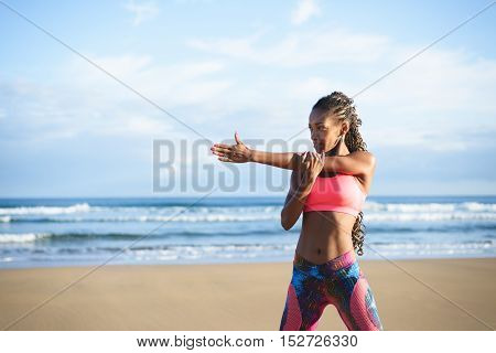 Fitness woman stretching arm and shoulder at the beach. Black female athlete working out outdoor against the sea.