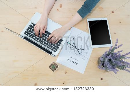 Office table with businessman's hand typing on keyboard and resume information and blank screen on tablet Purple lavender flower on pot. find job concept. View from above office table.