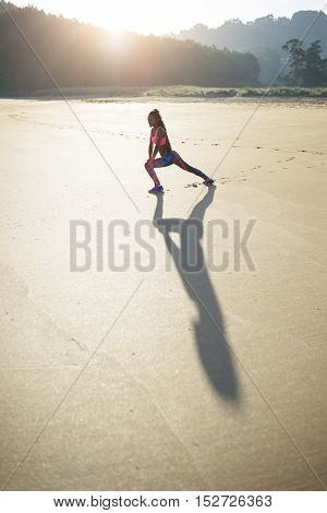 Sportswoman stretching legs on the beach for warming up before running. Fitness woman against sunrise morning sun.