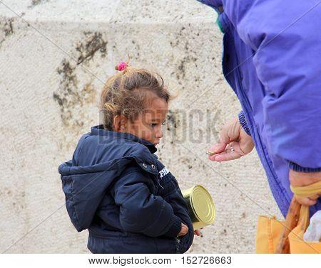 SKOPJE MACEDONIA - OCTOBER 18 2016:Older woman gives money to cute beggar girl downtown of Skopjecapital of Macedonia