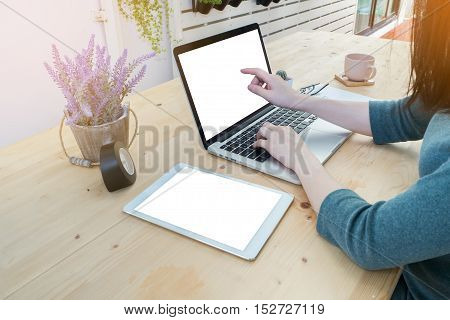office table with office equipment and woman 's hand touch on blank screen laptop working woman's hand touch screen laptop and coffee break lavender flower on pot at tree garden.