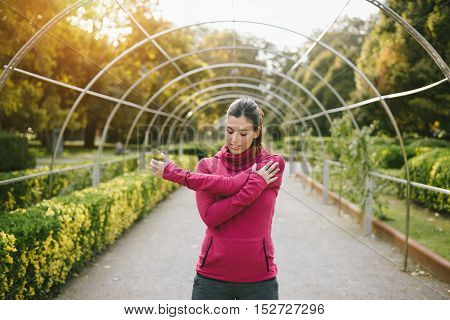 Fitness pregnant woman doing stretching exercise for arms and shoulder outdoor at urban park on early autumn. Gravid female athlete training outside.