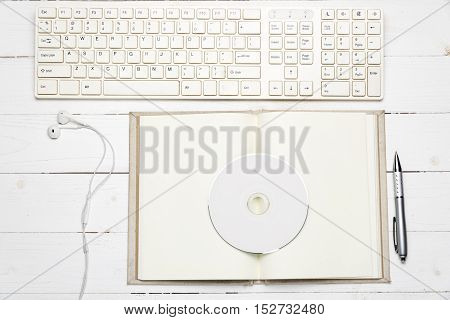 keyboard computer with open notebook and dvd disc on white wood background