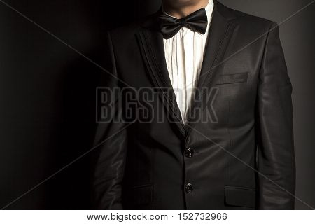 man wearing a black suit and bow tie on black background