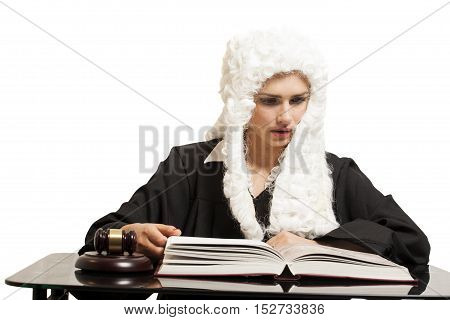 Female judge wearing a wig and black mantle with judge gavel and book on white backgriund