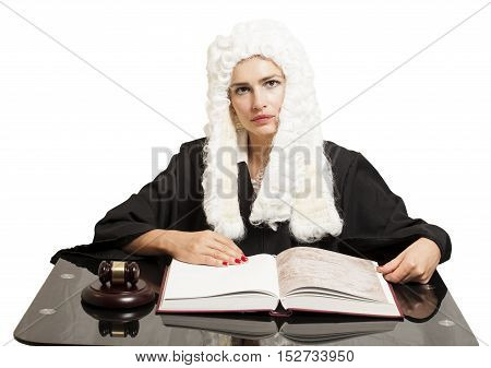 Female judge wearing a wig and black mantle with judge gavel and book isolated on white background