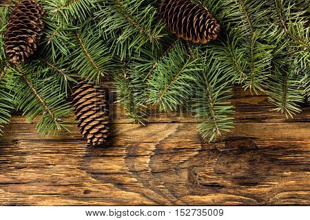 Christmas New Year background. Christmas tree branches. Fir tree branches and fir cones on wooden rustic background. Top view, copy space