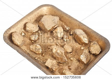 Golden nuggets on grungy wash pan with sand isolated on white background