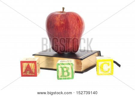 Red apple on book and ABC wooden letter blocks isolated