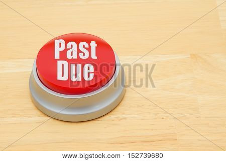 A past due red push button A red and silver push button on a wooden desk with text Past Due