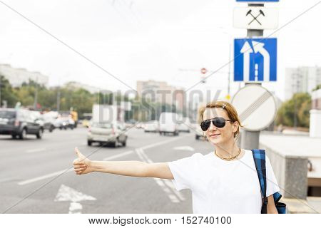 woman standing in the street calling taxi