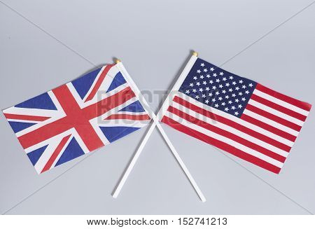 British (UK) and American flags on gray background