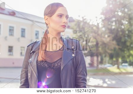 beautiful shot of a girl with bright trendy makeup in black leather skirt in glam-rock style luchas sunlight at sunset