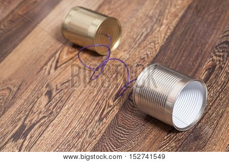 Tin Can Phone Wooden Background. Communication concept