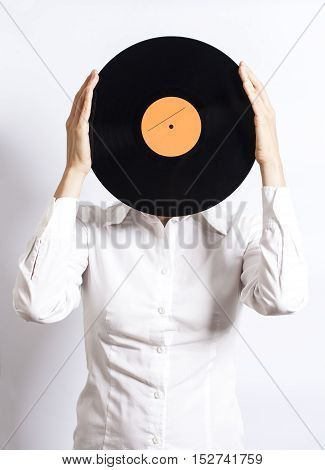 woman holding vinyl record over face on white