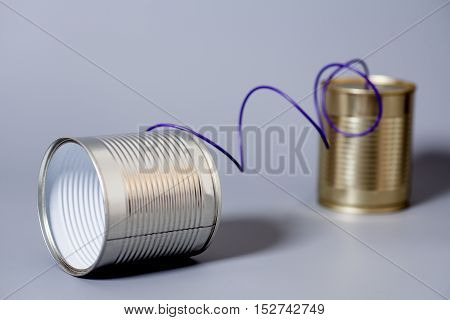 tin can phone on gray . communication concept