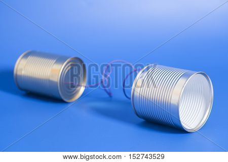 tin can phone on blue background. communication concept