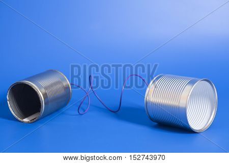 tin can phone on blue .communication concept