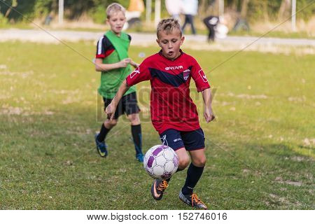 Lviv Ukraine - 30 Septemberl 2016: Boy hits the ball during a game of footballl on the playground near the school Lviv.