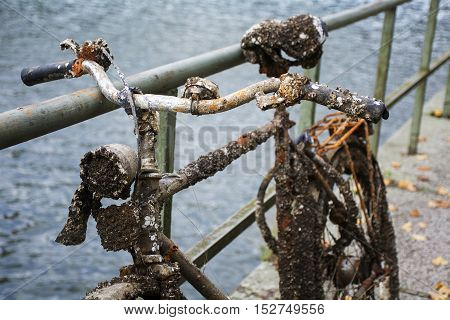 Old discarded bicycle leaning against a railing at the water full of rust small clams and barnacles found in the canal detail shot with selected focus and narrow depth of field