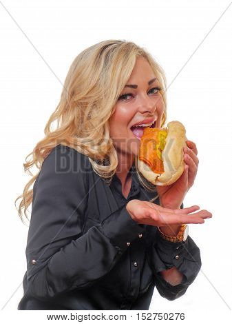 A blond haired woman is eating a deli styled sandwich.