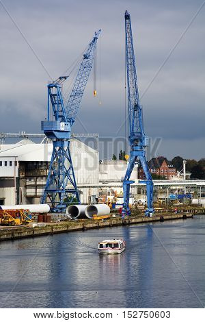 Luebeck Germany October 20 2016: Two blue cranes and a tourist ship on the river trave in the cargo port of Luebeck