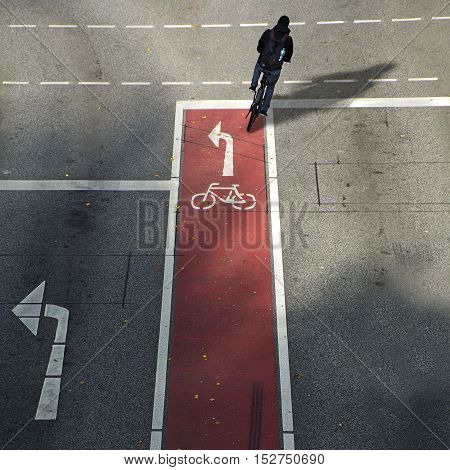 anonymous cyclist from behind on a bike lane with symbol and arrow driving in the wrong direction on the asphalt road concept for driving school and traffic safety