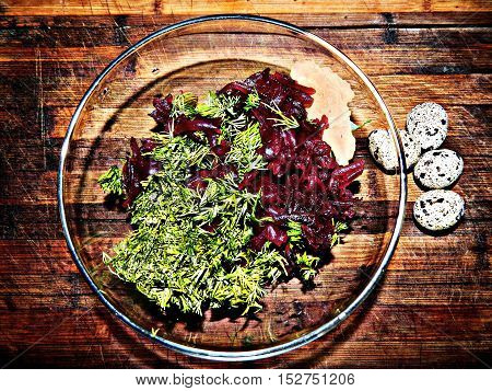 Ukrainian breakfast. In a transparent plate on a wooden chopping board grated cooked beets with fresh chopped dill and boiled quail eggs. Healthy food.