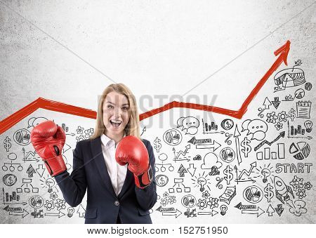 Woman in red boxing gloves is standing near concrete wall with red growing graph and startup sketches under it. Concept of successful business. Mock up